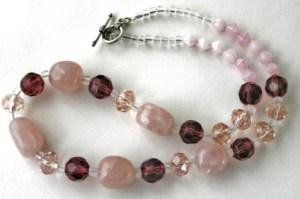 Korukivenä vaaleanpunaista kvartsia. Lisäksi vaaleanpunaisia ja luumunvärisiä lasihelmiä.