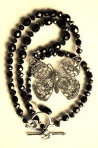 Mustia lasihelmiä ja filigraaniperhonen.