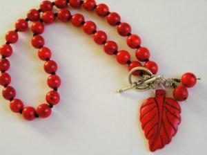 Punaista howliittia helminä, sekä riipuksena, joka on koristeellisen salpalukon yhteydessä katseenvangitsijana.