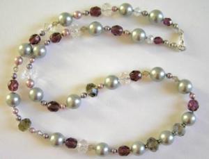 Makeanveden helmiä, sekä osoja harmaita simpukankuorihelmiä. Lisäksi lasia ja Swarovskin kristalleja. Lukko Sterling-hopeaa.