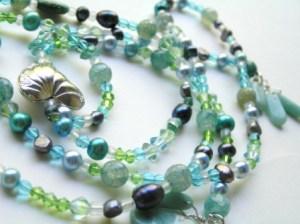 Erilaisia veden värisiä helmiä, kuten makeanveden helmiä, kristalleja pieniä akaatteihelmiä ja lasia. Pitkä kaulakoru, jossa riipuksena iso hopeoitu sydän.