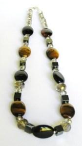 Tiikerinsilmä-, hemalyke- (hematiitti), ja kristallihelmiä. Väritys ruskea-harmaa.